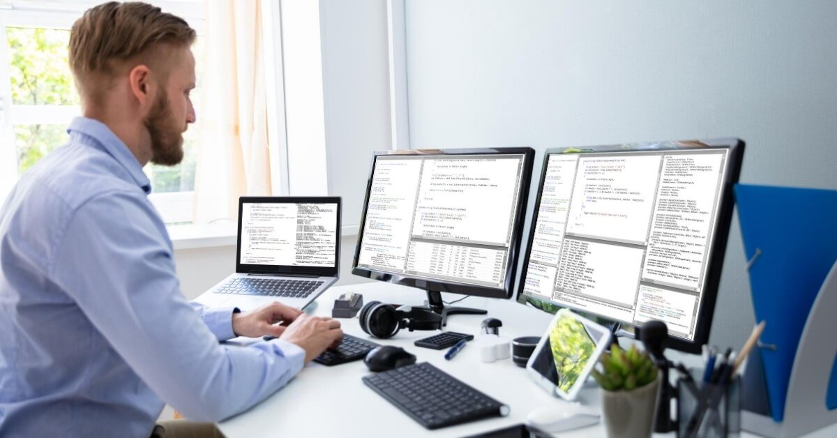 Software developer working from home on three screens simultaneously