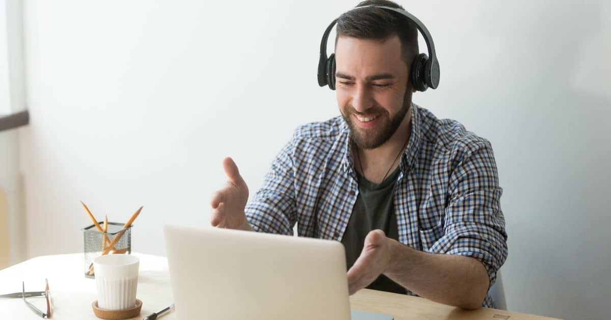 Bearded man with headphones gesturing to his laptop as if having a conversation