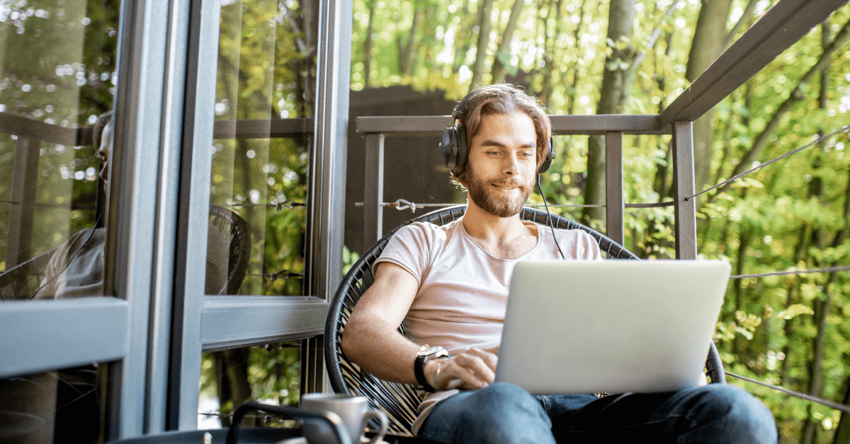 Software developer sitting outside on balcony working in front of his laptop with headphones