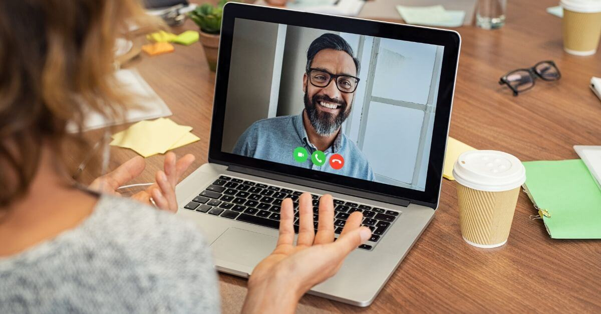 Woman chatting with a bearded man in video conference on her laptop