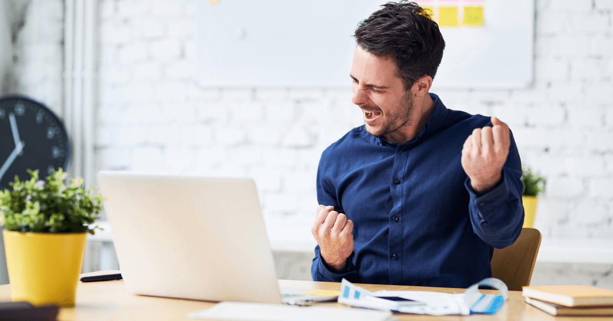 Developer in front of laptop with blue dress shirt celebrating success
