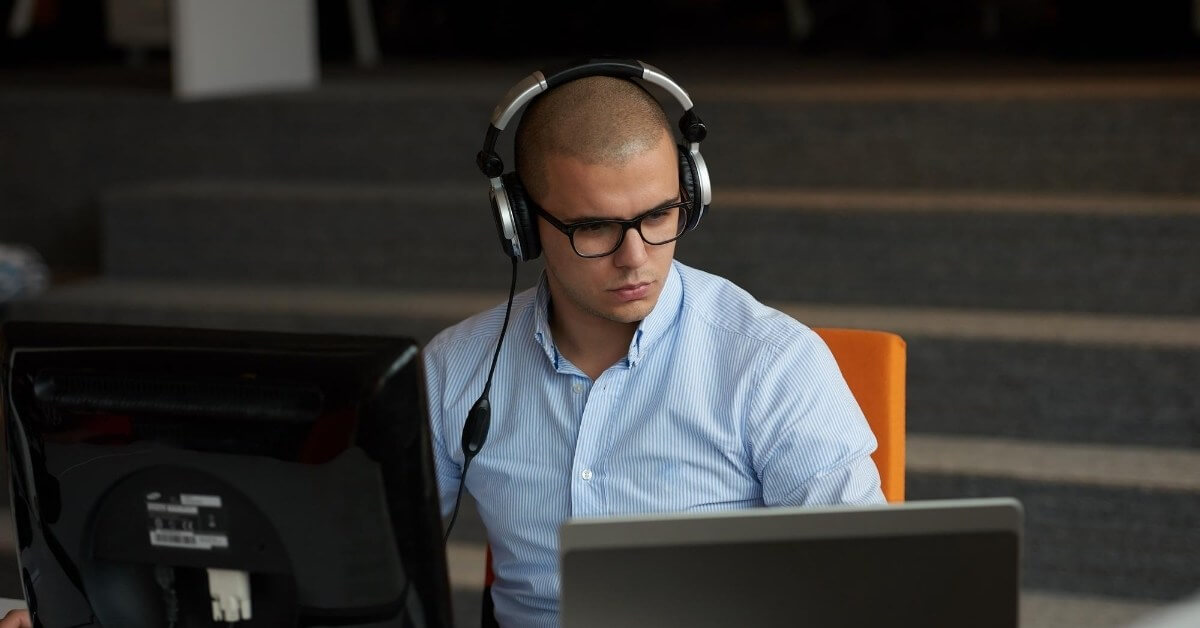image showing developer in front of a computer with earphones on