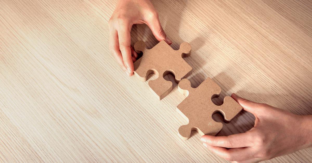 hands fitting together wooden puzzle pieces over wooden desk